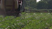 postřikovačů : Agricultural tractor with crop sprayer attached spraying pesticides on sunflower plants in cultivated field Dostupné videozáznamy