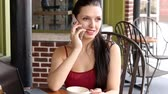 telemóvel : Beautiful young European woman talking on mobile phone at cafe