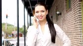 tampa : Positive businesswoman talking on mobile phone walking in focus