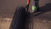 eyaletler arası : Worker rolls the mesh on the road before laying the asphalt Stok Video