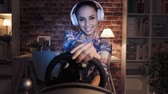 dostihy : Woman playing video games using a wheel steering wheel, she is enjoying and smiling, gaming and entertainment concept Dostupné videozáznamy