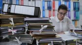 effizient : She is working on the desk and writing documents, she has stacks of paperwork on her desk: work overload concept Stock Footage