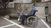 querido : Man in wheelchair meeting his female friend outdoors and talking, handicap and relationships concept