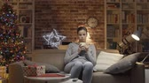 entediado : Disappointed woman having a lonely Christmas at home and drinking coffee, she is not receiving any message on her smartphone Stock Footage