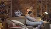 calendrier : Sad woman having a Christmas Eve at home on a sofa Vidéos Libres De Droits