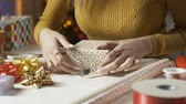 ajándékdobozban : Young woman preparing Christmas gifts at home, she is folding wrapping paper, holidays and celebration concept Stock mozgókép