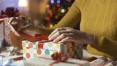 wstążka : Woman putting a Christmas card into an envelope and preparing gifts Wideo