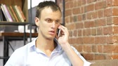 перегружены : Disappointed, Unhappy, sad man talking on cellphone at creative work place