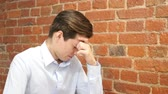 перегружены : Overwhelmed young businessman with headache thinking  at his office Стоковые видеозаписи