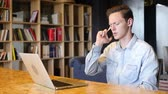 sekreter : Young worker talking on phone in front of laptop