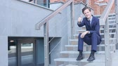 неузнаваемый : Thumbs Up by Young Businessman Sitting on Stairs Outside Office