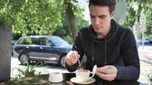 чай : Young Man Mixing Sugar and Drinking Coffee, Sitting in Cafe Terrace Стоковые видеозаписи