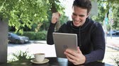 терраса : Excited Man Celebrating Success on Tablet Sitting in Cafe Terrace Стоковые видеозаписи