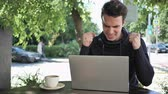 терраса : Excited Man Celebrating Success on Laptop Sitting in Cafe Terrace