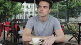 терраса : Young Man Sitting in Cafe Terrace and Looking Around Стоковые видеозаписи