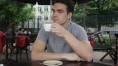 гидратация : Young Man Drinking Coffee while Sitting in Cafe Terrace Стоковые видеозаписи