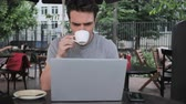 терраса : Man Drinking Coffee and Working on Laptop while Sitting in Cafe Terrace
