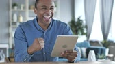 tab : Young African Man Excited for Success while Using Tablet