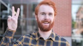 bem : Sign of Victory by Redhead Beard Young Man Standing Outdoor