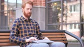 werk : Redhead Beard Young Man Leaving Bench after Closing Laptop Stockvideo
