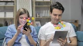 receber : Young Couple Using Smartphone and Tablet, Flying Smileys, Emojis and Likes