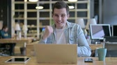 pagina web : Surprised Young Designer Celebrating Success on Laptop in Office