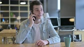 negotiation : Cheerful Young Designer talking on Smartphone in Office Stock Footage
