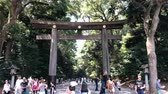 Travellers walk through torii shrine gate at Meiji Jingu Shrine temple, Japan