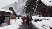 Tourists walking at historic village during snowing in winter season