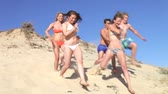 traje : Group of teenage friends standing at the top of dune before running down and past camera.
