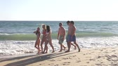 traje : Boys following girls along shore admiring the view and making comments. Stock Footage