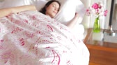 безмятежность : Camera tracks along bed to sleeping woman snuggled under duvet.