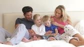 acordo : Children sitting between parents in bed reading a book together.