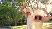 dráha : Two women wearing sunglasses and straw hats dance along country path. Dostupné videozáznamy