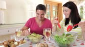 dieta : Couple seated around dining table serving one another before woman picks up glass of wine.