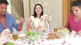 жена : Couples seated around dining table serving one another before picking up glasses for toast. Стоковые видеозаписи
