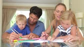 quatro pessoas : Father helping son and mother help daughter as they work on picture with pens together.