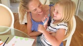 craft : Mother bounces daughter on knee as they sit at table working on picture with pens together.