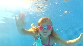dámské plavky : Underwater view young girl wearing goggles waving at camera.