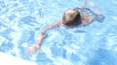 dámské plavky : Young girl wearing goggles swims to edge of pool and waves at camera.