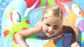 traje : Girl in inflatable rubber ring paddles towards camera before moving away and waving. Stock Footage