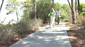 cyklus : Long shot of romantic senior couple cycling along country path towards camera.