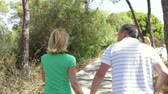 dráha : Rear view of romantic senior couple holding hands as they walk along country path. Dostupné videozáznamy
