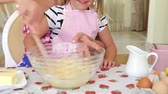 середине взрослых : Close up of mother mixing ingredients in bowl with wooden spoon. Стоковые видеозаписи