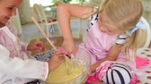 яйцо : Two girls sitting at kitchen table mixing ingredients in bowl with wooden spoon and whisk. Стоковые видеозаписи