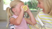 piada : Grandmother and granddaughter sitting at kitchen table with ingredients as girl holds up lemon halves and makes funny face. Stock Footage