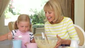 яйцо : Grandmother and granddaughter sitting at kitchen table as girl adds ingredients to bowl.