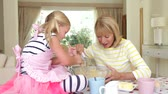 ovos : Grandmother and granddaughter sitting at kitchen table as they whisk mixture in bowl.