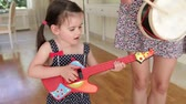 canção : Daughter plays toy guitar and sings whilst mother plays drum.