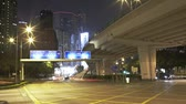 hong kong : Traffic speeds across junction as night capturing light trails as it passes traffic lights.